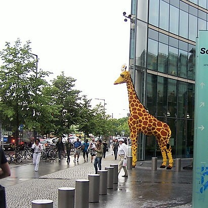 A life-sized model of a giraffe stands in a busy public plaza.