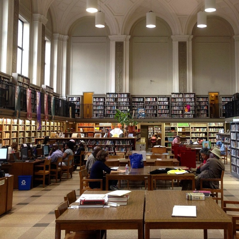 Tall cases of books surround a central area full of desks as people sit reading and accessing information from computers in a public library.