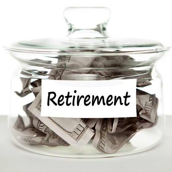 "A glass jar labeled ""retirement"" is filled with cash."