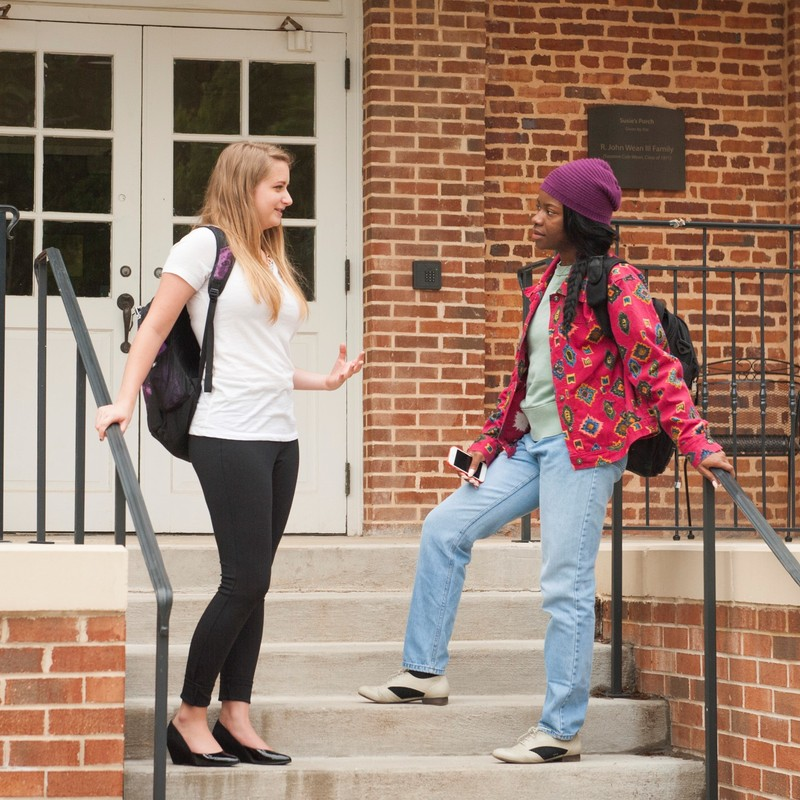 A pair of female students stand on the steps in front of a building engaged in conversation.