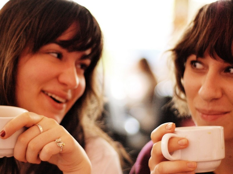 Two close friends have a conversation over coffee.