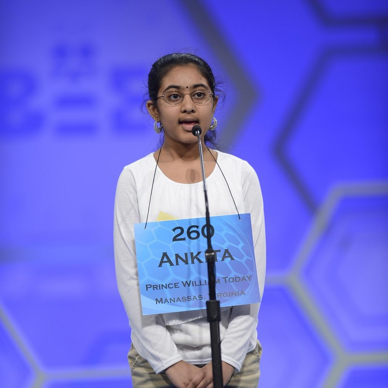 A girls stands on stage in front of a microphone as she attempts to spell a word in the Scripps National Spelling Bee.