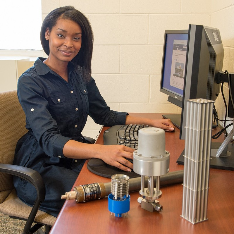 J'Tia Taylor sits at her desk. She is a nonproliferation technical specialist at an engineering research laboratory.