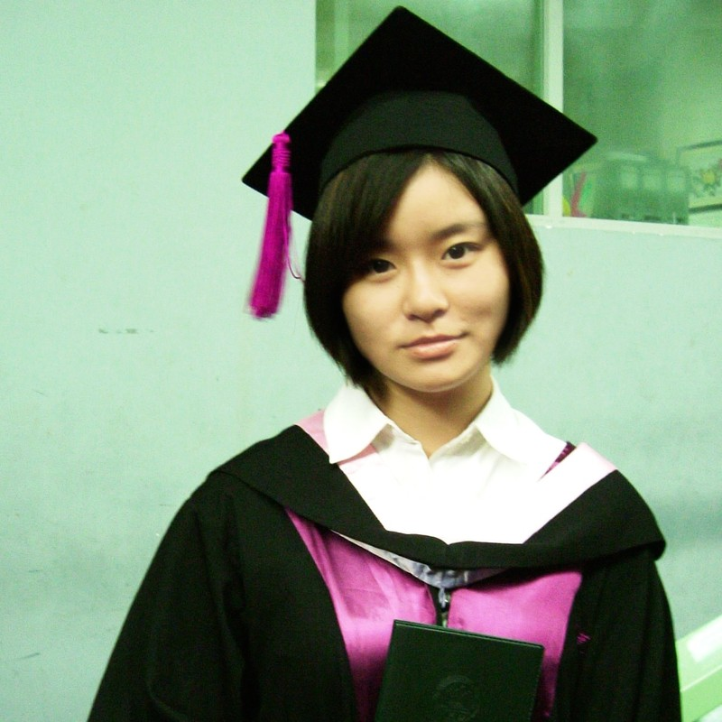 An East Asian woman dressed in a graduation cap and gown wears a neutral or subdued expression.