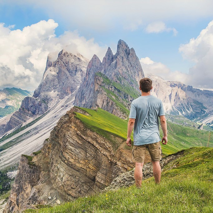 A man stands in an alpine meadow and looks into the distance at the high mountain peaks.