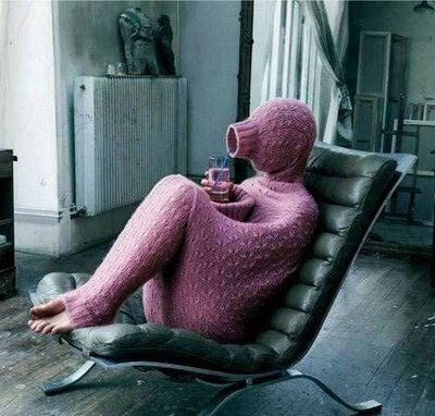 A person sits on a chair almost completely hidden inside a long sweater.