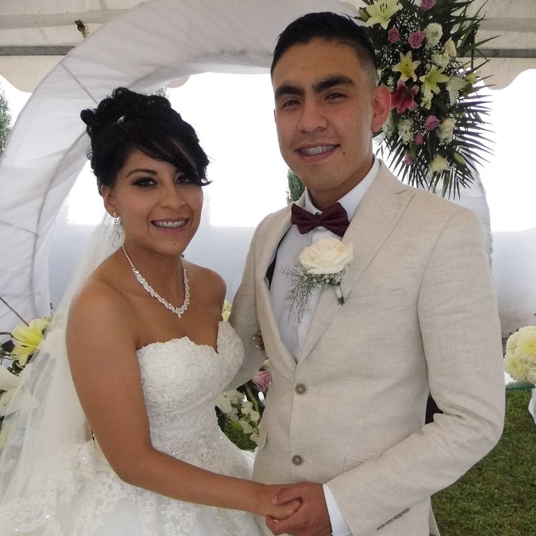 A bride and groom happily posing for the camera on their wedding day.