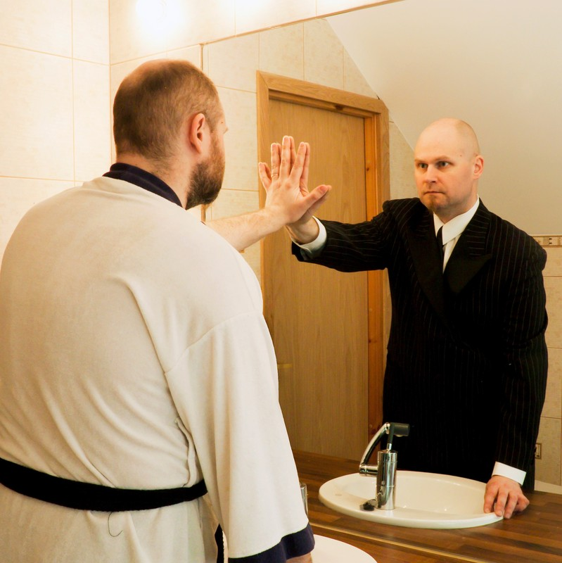 A man stands in front of the bathroom mirror and reaches out to touch an altered reflection of himself.