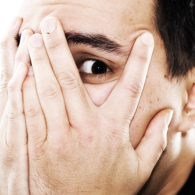 A man covers his face with his hands and peeks out from behind his fingers.