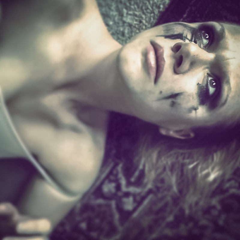 A distraught looking woman lies on the floor with makeup smeared across her face.