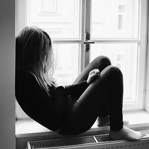 A young woman sits alone on a windowsill.
