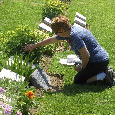 A woman kneels in front of a headstone in a cemetery.