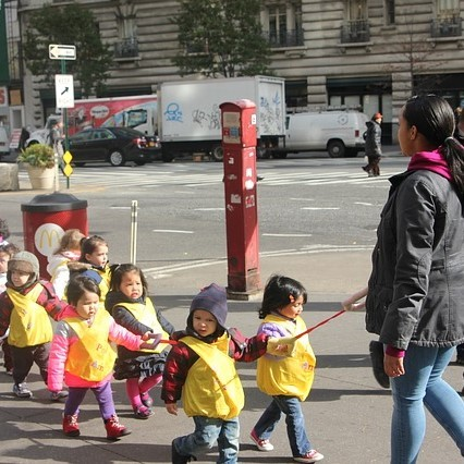 A group of preschool students are lead along a city street by an adult.