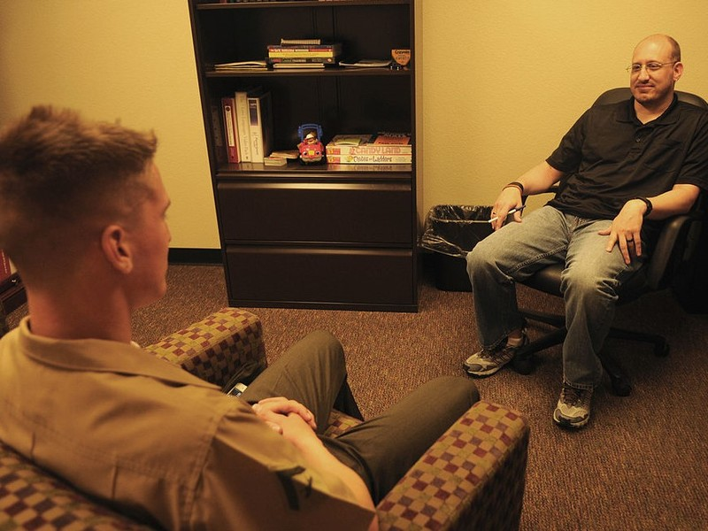 A therapist and patient sit facing one another during a session.