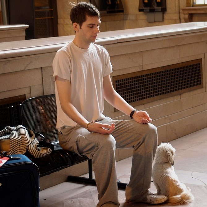 A young man meditates on a bench in a train station.