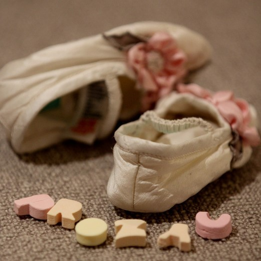 "Image of baby booties and the word ""Prozac"" spelled out in candy letters."