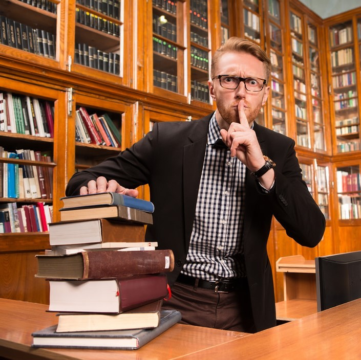 A man dressed in a jacket and bow tie stands behind a desk stacked with books. He has a stern look on his face and is putting a finger to his lips requesting quiet. Behind the man are shelves lined with books.