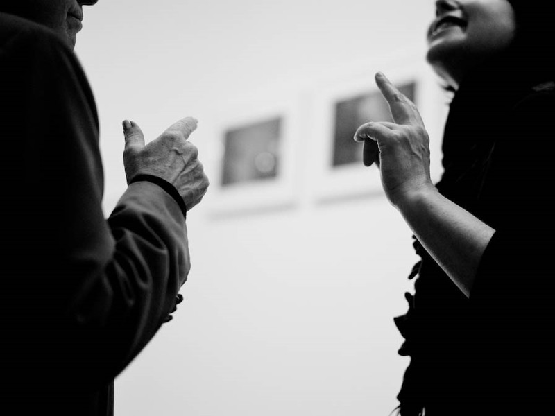 A man and woman are engaged in conversation and making identical hand movements.