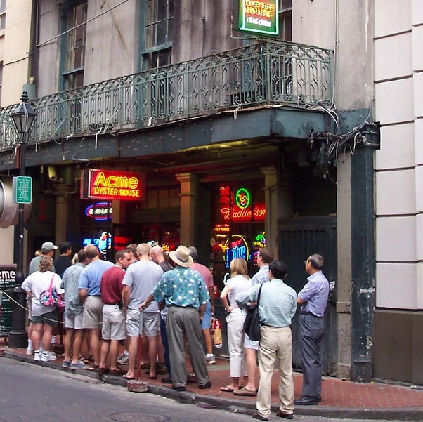 A long line of people stand on the sidewalk in front of a restaurant waiting to get in.
