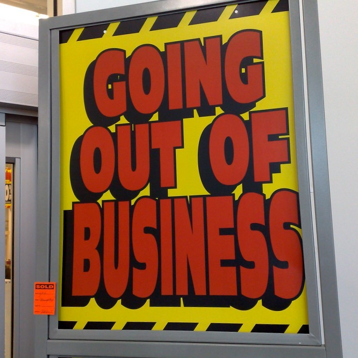 "A ""Going out of Business"" sign is posted outside a store."