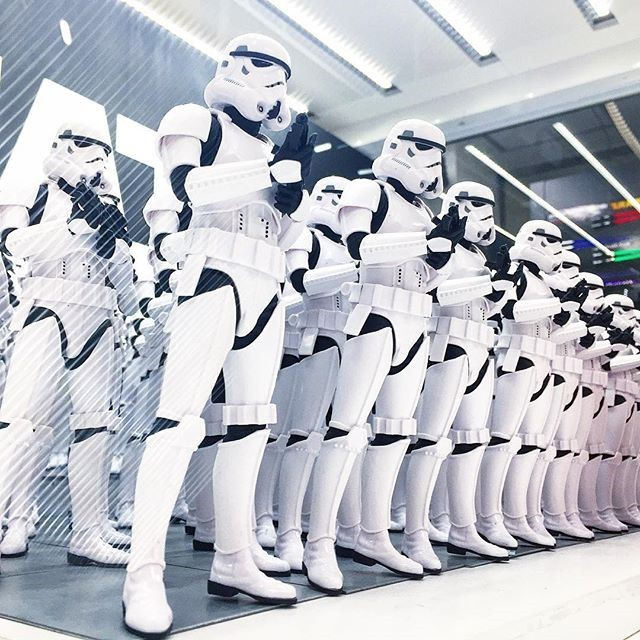 A line of identically dressed stormtroopers from the Star Wars films.