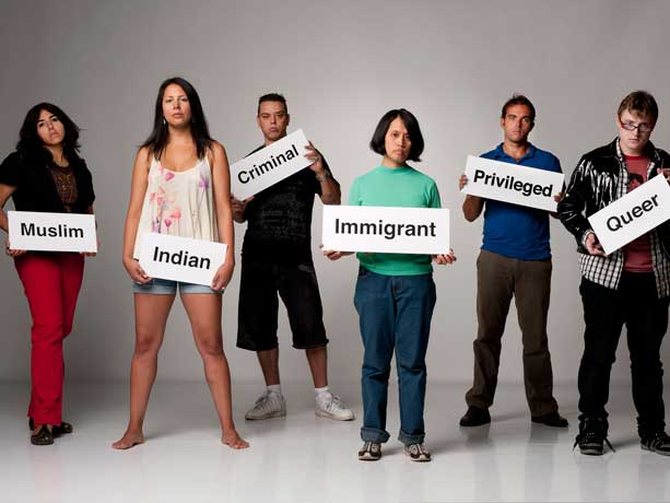 "A group of people stand holding signs labeling them as others perceive them. The signs include, ""Muslim"", ""Indian"", ""Criminal"", ""Immigrant"", ""Privileged"", and ""Queer""."