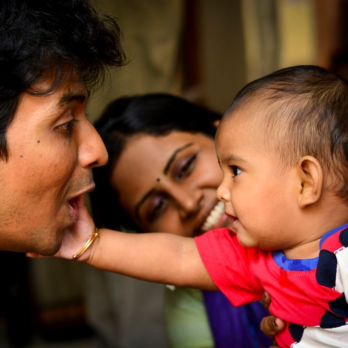 A baby reaches out to touch the face of his smiling father as a happy mother looks on.