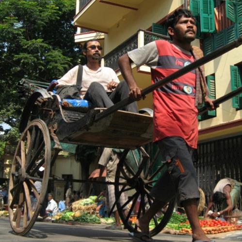 A rickshaw driver pulls a passenger down a city street.
