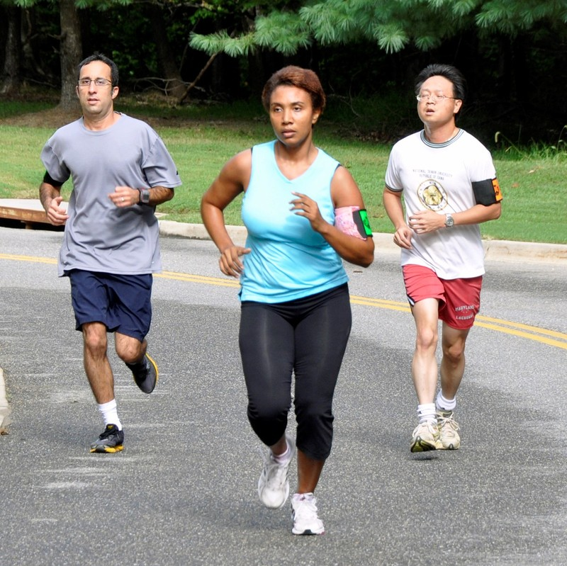 A group of joggers running through a park.
