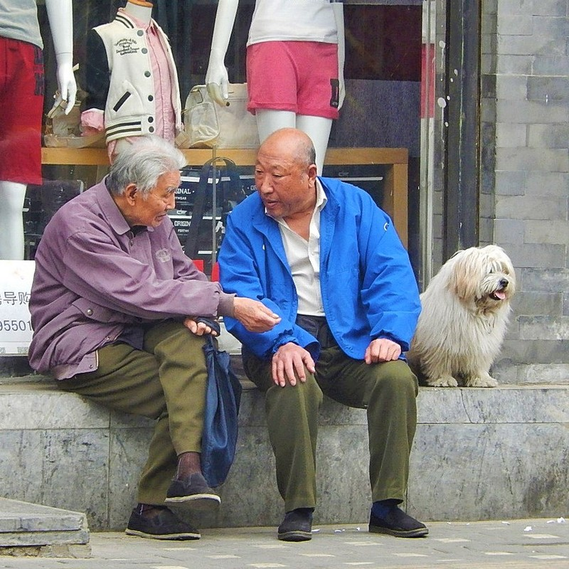 Two older men sit together in front of a shop having a conversation.