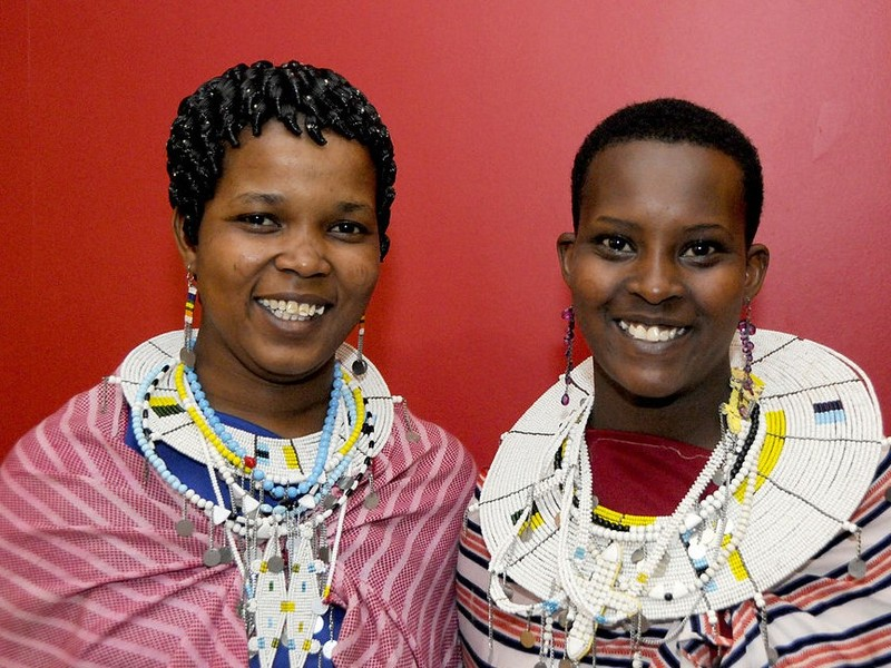 Two teen aged Maasai girls pose together in traditional clothing.