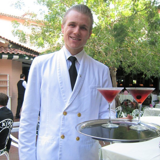 A smiling waiter delivering cocktails on a tray.