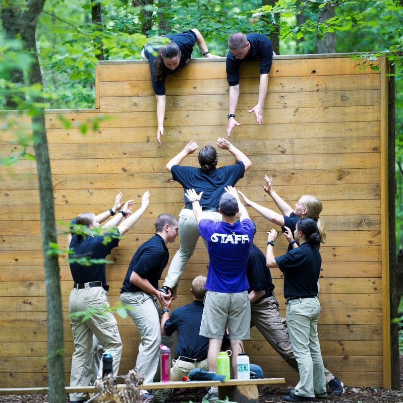 A team of people on an obstacle course work together to boost one member of the group over a high wall.