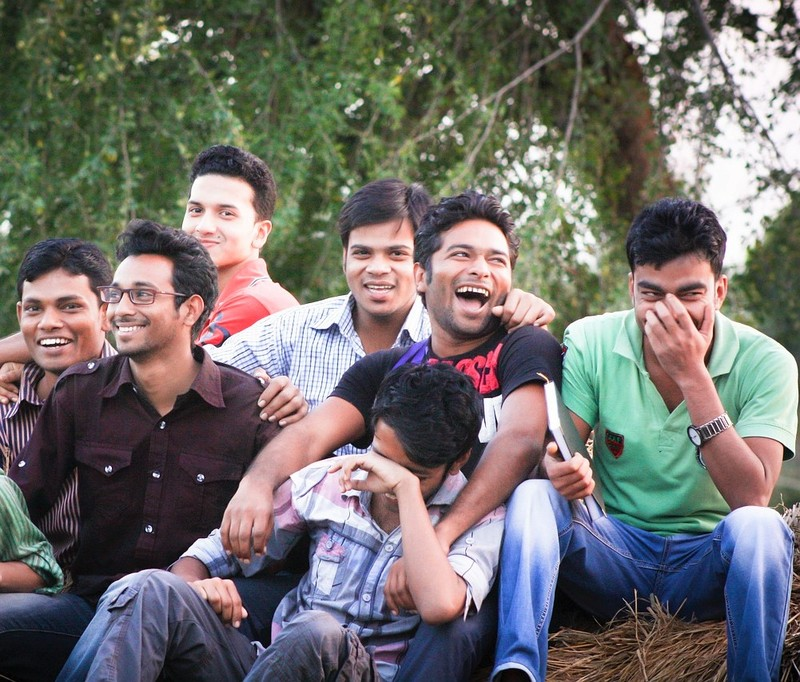A group of young men sit together laughing and smiling.