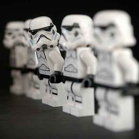 A line of identically dressed stormtroopers from the Star Wars films. One stormtrooper is stepping out of formation and looking at the others in the group.