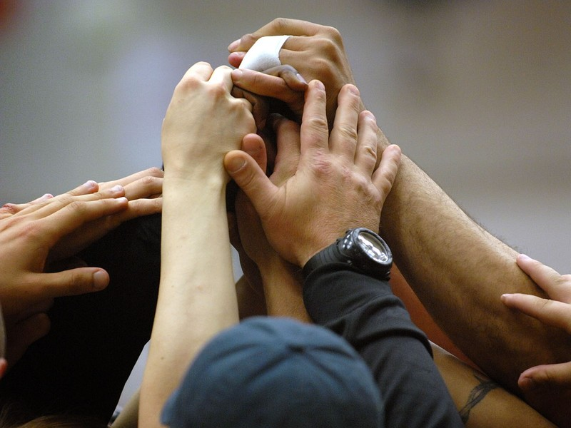 Members of a softball team put their hands together in the center of a circle to signify unity.