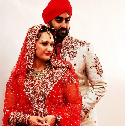 A young couple posing for wedding photos in traditional Indian attire.