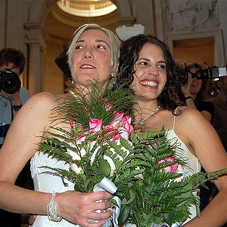 A bride and bride dressed in traditional white wedding gowns hold bouquets of flowers and smile for photos after a wedding ceremony.