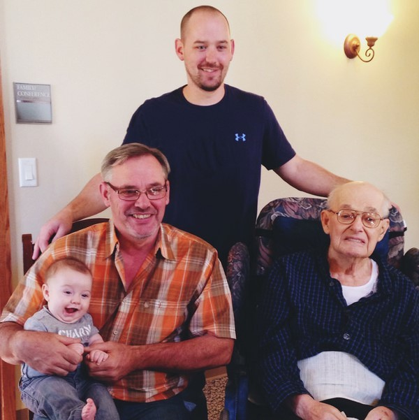 A family photo of four generations of men from great grandfather to great grandson.