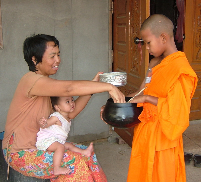 A Buddhist woman with a baby on her lap places food into the alms bowl of a young Buddhist priest dressed in traditional orange robes.