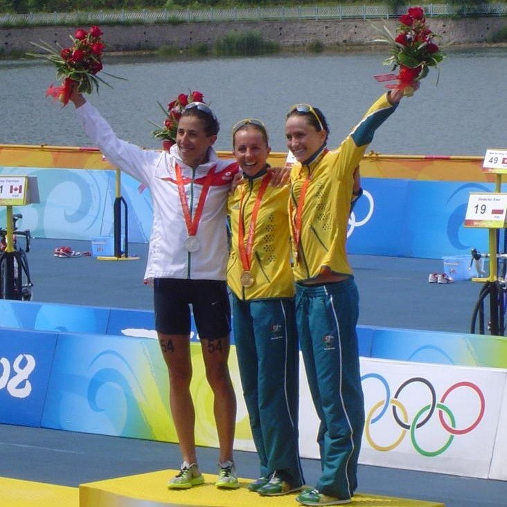 The three medalists in the 2008 Women's Olympic Triathlon stand together on the winner's podium.
