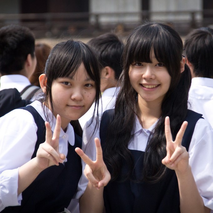 "Two Japanese school girls smile and flash a typical ""V-sign"" as the pose for a photo."