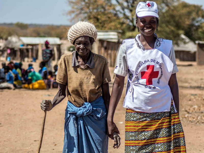 A Red Cross volunteer assists an elderly lady from Mozambique, where a food distribution was taking place.