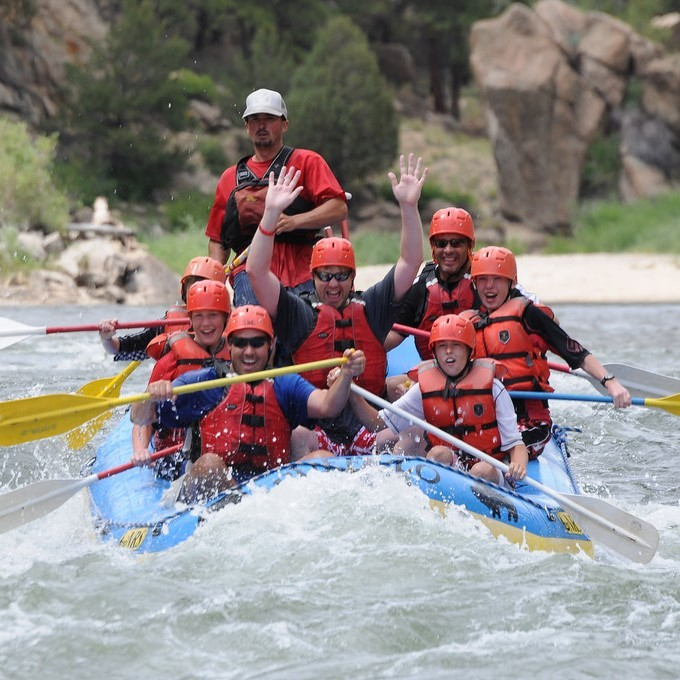 A group of white water rafters paddle together in rough waters.
