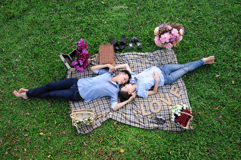 A romantic couple lying on a picnic blanket surrounded by bouquets of flowers.