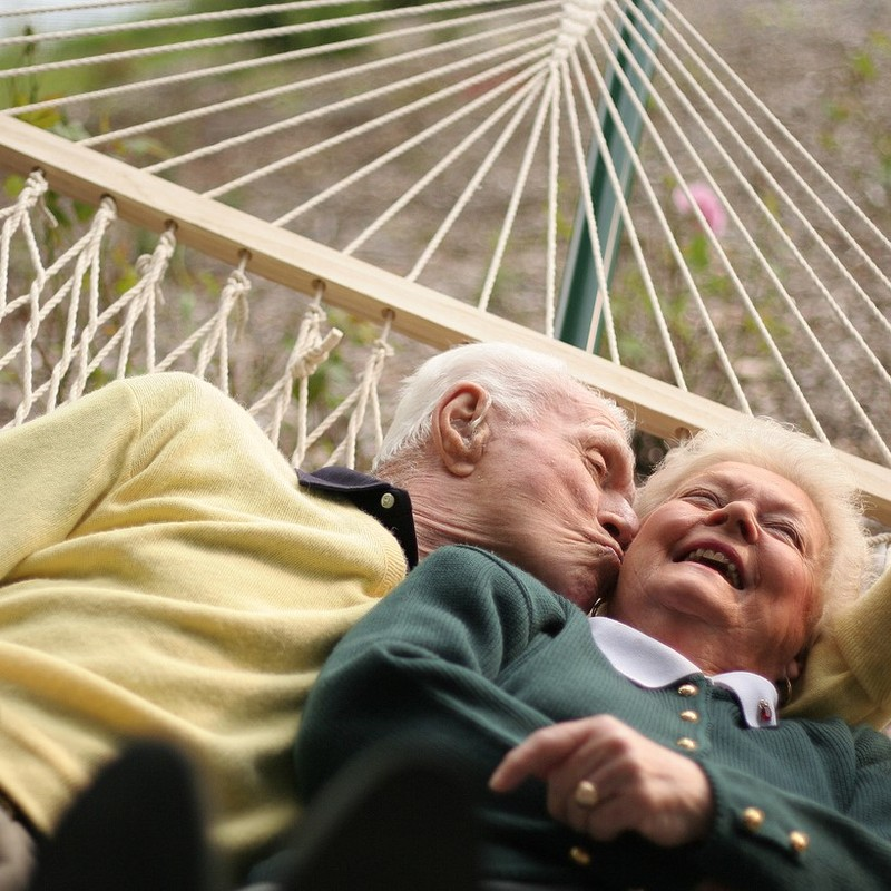 An elderly couple lie together in a hammock. The man kisses the woman on the cheek as she laughs.