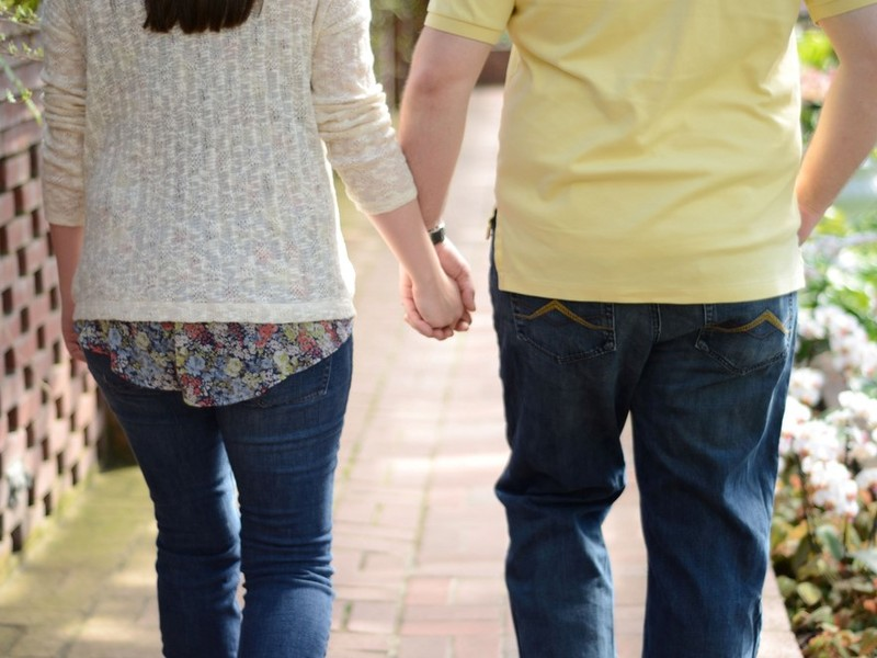 A couple holding hands as they walk down the sidewalk.