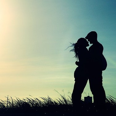 A silhouette of a couple embracing seen against the evening sky.