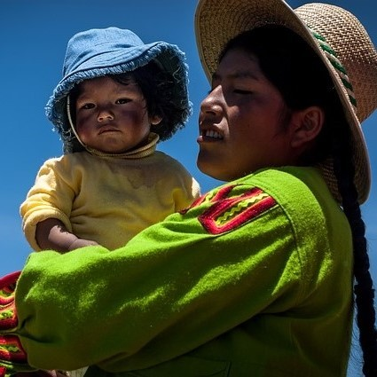 A woman dressed in traditional Bolivian clothes and hat holds her baby in her arms.