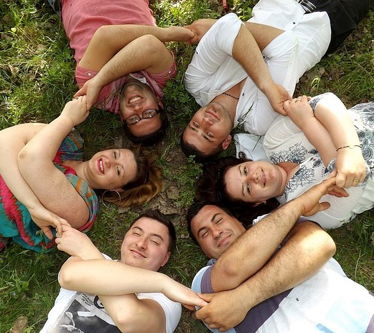 A group of friends lay together on the grass in a circle holding hands.